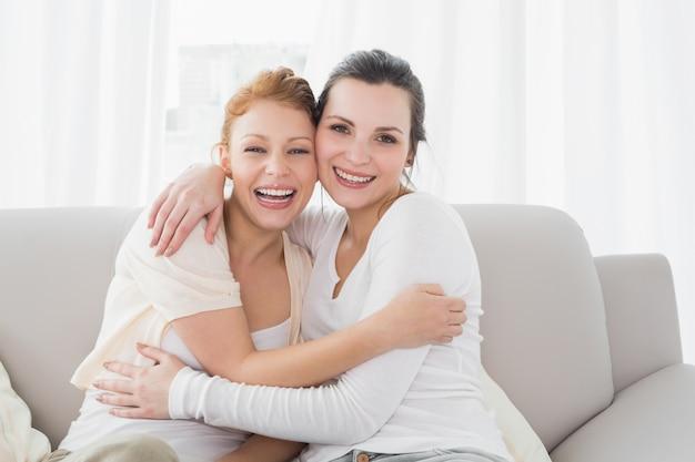 Vrolijke vrouwelijke vrienden die in woonkamer omhelzen