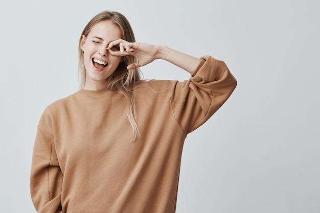 Vrolijke vrouwelijke vrouw met blond steil haar, verheugt zich met succes voor examens, blij met een ontmoeting met groepsgenoten, breed glimlachend. opgetogen mooie blonde vrouw heeft een speelse uitstraling