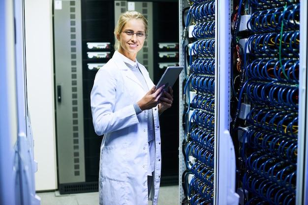 Vrolijke vrouwelijke wetenschapper in datacenter