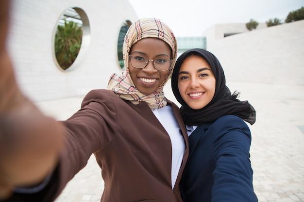 Vrolijke vrouwelijke zakelijke vrienden nemen selfie
