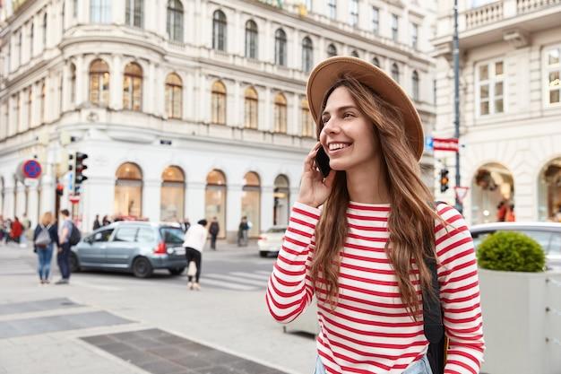 Vrolijke vrouwelijke zwerver slentert in de stad, geniet van communicatie, houdt moderne smartphone in de buurt van oor, opzij gericht