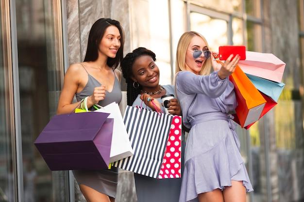 Vrolijke vrouwen bij winkelen die selfie nemen