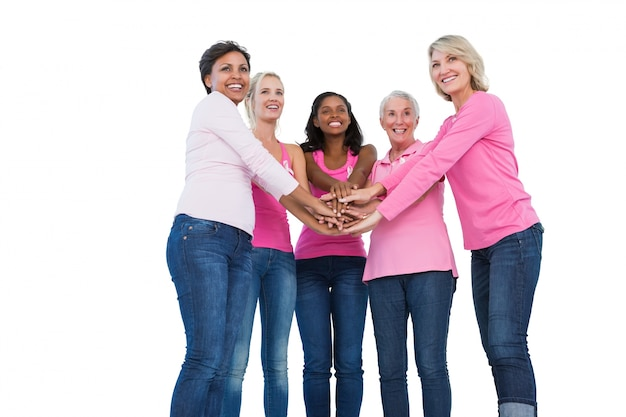 Vrolijke vrouwen die de linten van borstkanker met handen samen dragen