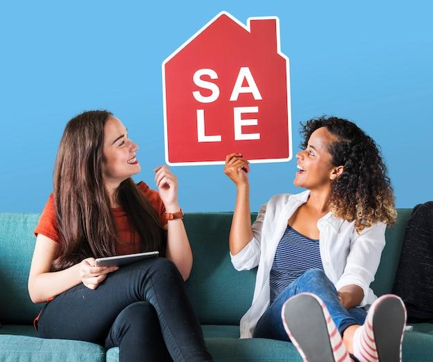 Vrolijke vrouwen die een pictogram van de huisverkoop houden