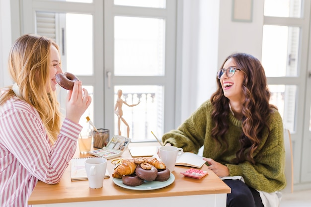 Vrolijke vrouwen die gebakje trekken en eten