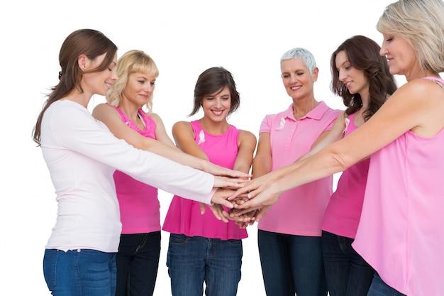Vrolijke vrouwen die in cirkel stellen die roze voor borstkanker dragen