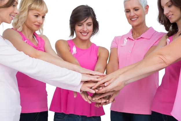 Vrolijke vrouwen die in de handen van de cirkelholding stellen die roze voor borstkanker dragen