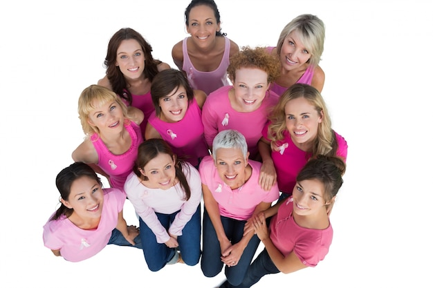 Vrolijke vrouwen die omhoog dragend roze voor borstkanker kijken