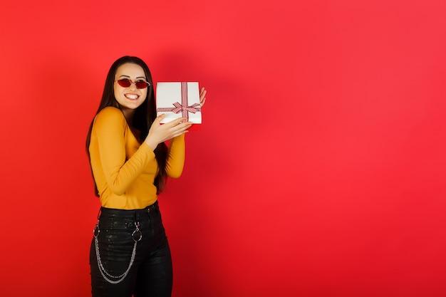 Vrolijke vrouwen gele blouse en rode bril is een witte geschenkdoos met rode strik.