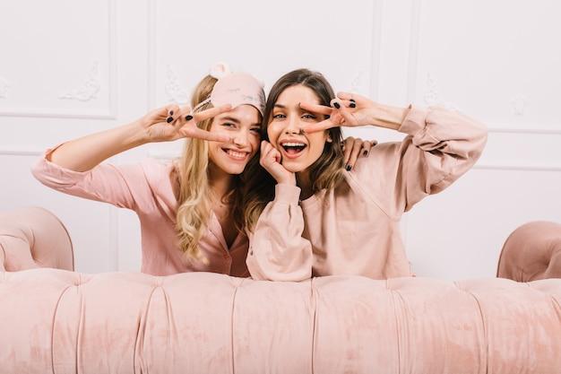 Vrolijke vrouwen in pyjama's die vredestekens tonen