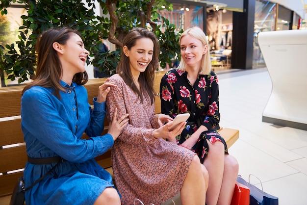 Vrolijke vrouwen kijken naar de mobiele telefoon