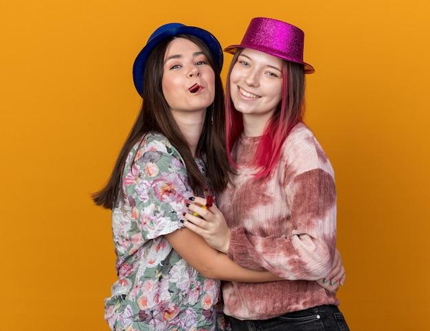Vrolijke vrouwen met feestmuts omhelsden elkaar geïsoleerd op oranje muur