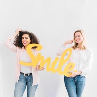 Vrolijke vrouwen met glimlach schrijven