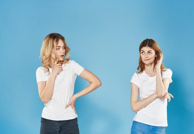 Vrolijke vrouwen modieuze kleding bijgesneden weergave blauwe studio achtergrond. hoge kwaliteit foto