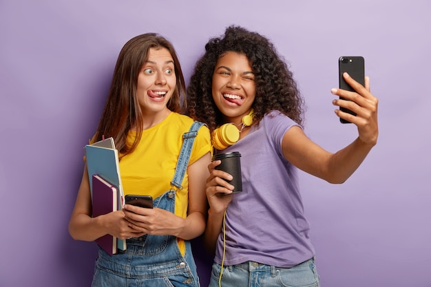 Vrolijke vrouwen studeren in één groep, hebben plezier tijdens de pauze op de universiteit, nemen selfie op smartphone, tonen tongen, houden papieren kopjes koffie vast, houden blocnotes vast, poseren samen tegen een paarse muur.