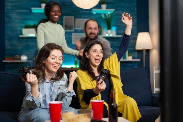 Vrolijke vrouwen vieren de overwinning tijdens het spelen van videogames met vrienden met behulp van een draadloze controller. groep vrienden van gemengd ras die 's avonds laat spelletjes spelen terwijl ze op de bank in de woonkamer zitten.