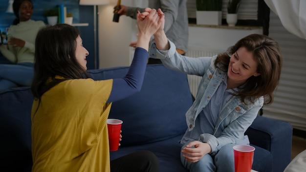 Vrolijke vrouwen vieren vriendschap met high five 's avonds laat in de woonkamer