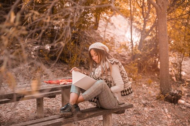 Vrolijke vrouwenlezing dichtbij lijst in de herfstbos