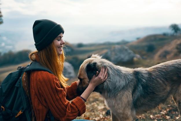 Vrolijke vrouwentoerist naast de leuke vriendschapsspelletjes van de hond