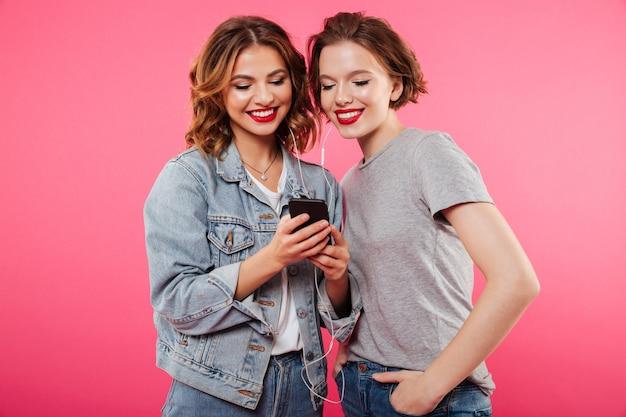 Vrolijke vrouwenvrienden die mobiele telefoon het luisteren muziek met behulp van.
