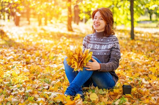 Vrolijke vrouwenzitting op gele bladeren