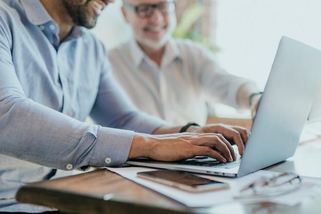 Vrolijke webontwikkelaars die op een laptop werken