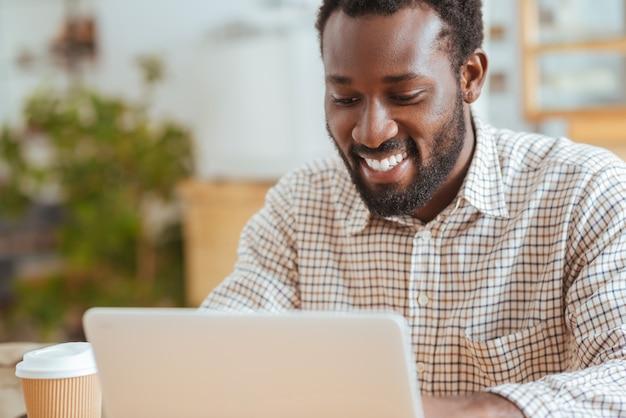 Vrolijke werknemer. de close-up van een charmante jonge man die in het café zit en gelukkig lacht tijdens het werken op de laptop