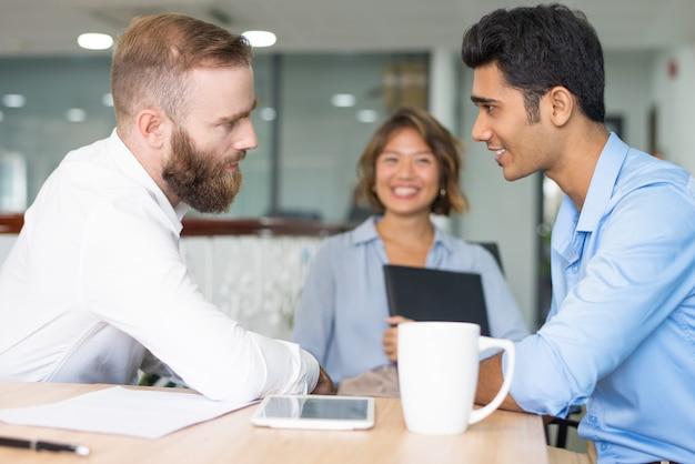 Vrolijke werknemer die aan het fronsen van werkgever rapporteert