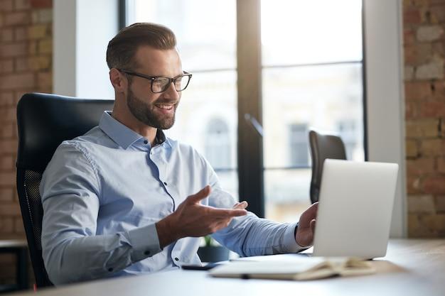 Vrolijke werknemer die naar het laptopscherm kijkt en glimlacht