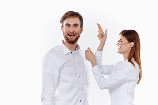 Vrolijke werknemers die met hun handen gebaren om een licht achtergrondshirt communicatiemodel te werken