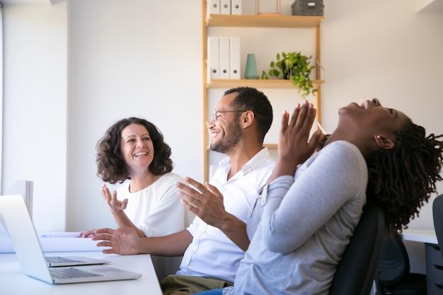 Vrolijke werknemers praten en lachen op de werkplek