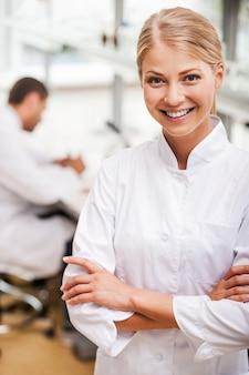 Vrolijke wetenschapper. mooie jonge vrouwelijke wetenschapper die de armen gekruist houdt en naar de camera kijkt terwijl haar mannelijke collega op de achtergrond werkt