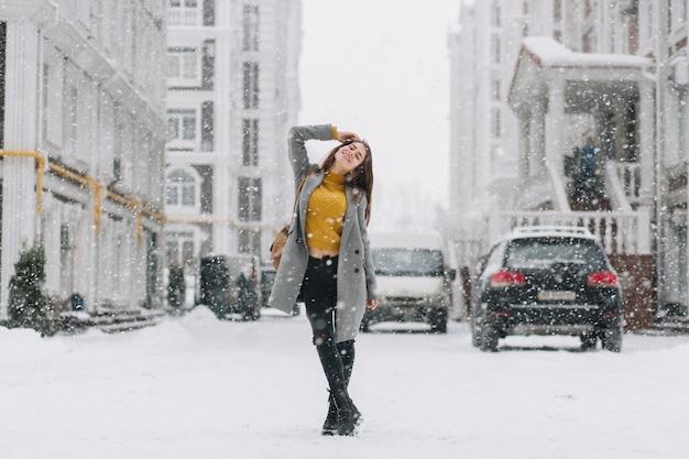 Vrolijke winter jonge vrouw koelen in sneeuwval op straat in de grote stad. modieus model met rugzak, lachend met gesloten ogen, genietend van sneeuwt, sneeuwvlokken, kerstsfeer.
