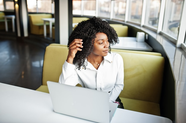 Vrolijke zakelijke afro-amerikaanse dame met afro haar, witte blouse zittend aan tafel dragen en werken met laptop in café.