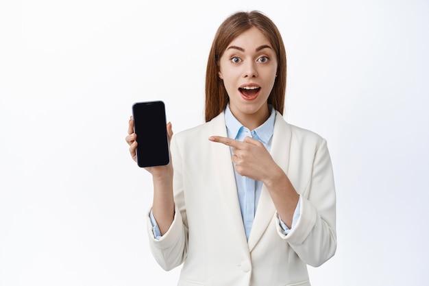 Vrolijke zakelijke vrouw in pak, wijst naar leeg scherm van mobiele telefoon en glimlach, app met opwinding tonen, staat tegen witte muur