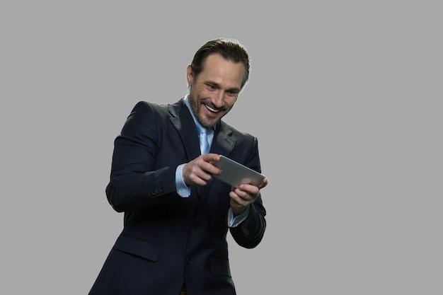 Vrolijke zakenman die een videogame speelt. opgewonden manager speelspel op smartphone tegen een grijze achtergrond.