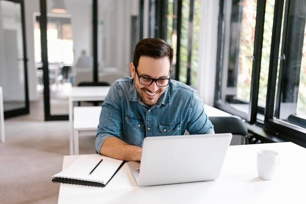 Vrolijke zakenman die laptop in heldere bureauruimte met behulp van.