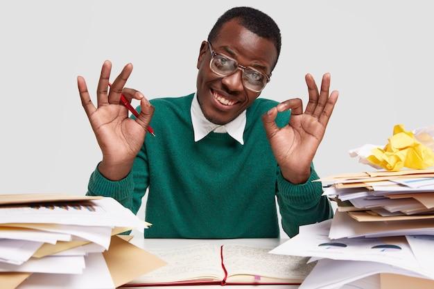 Vrolijke zakenman geeft ok gebaar, draagt groene trui, verzekert dat alles in orde is en hij is klaar om zijn projectwerk te presenteren