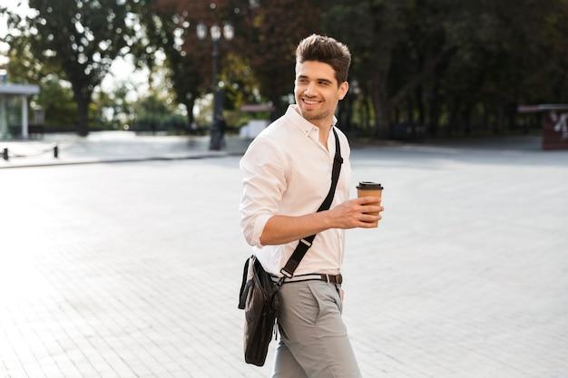 Vrolijke zakenman gekleed in shirt buiten lopen