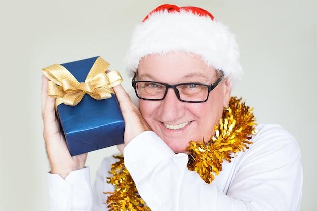 Vrolijke zakenman in kerstmanhoed die heden toont