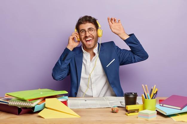Vrolijke zakenman zit aan het bureau