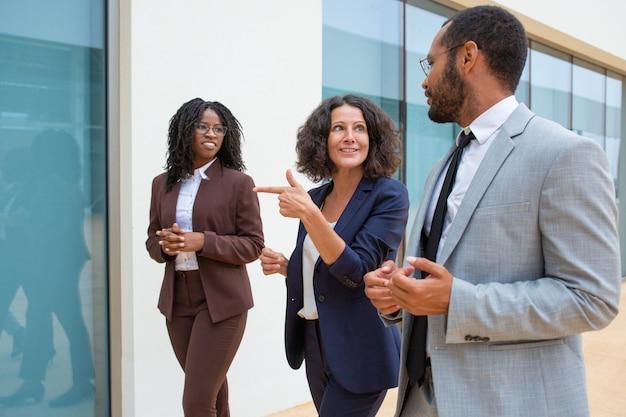 Vrolijke zakenmensen lopen en praten