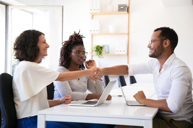 Vrolijke zakenpartners handen schudden