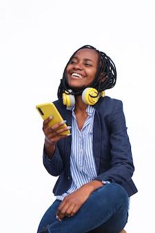 Vrolijke zakenvrouw die haar telefoon gebruikt met een koptelefoon in haar nek, zittend tegen een witte achtergrond