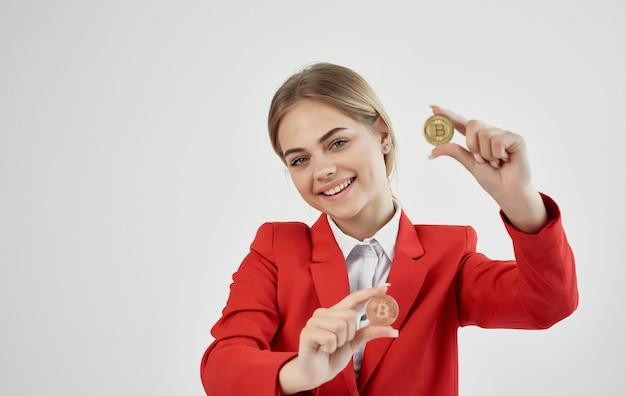 Vrolijke zakenvrouw in een rood jasje cryptocurrency bitcoin elektronisch geld.