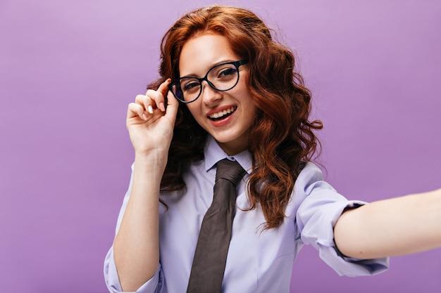 Vrolijke zakenvrouw in shirt en bril neemt selfie