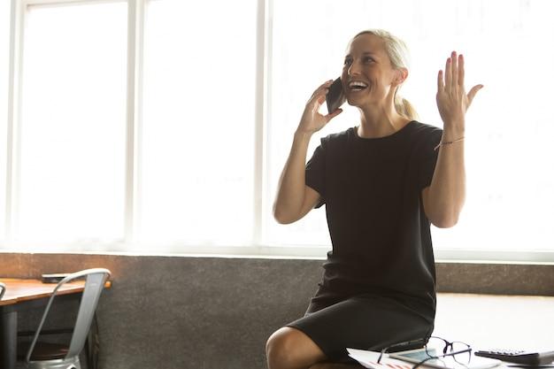 Vrolijke zakenvrouw praten over de mobiele telefoon