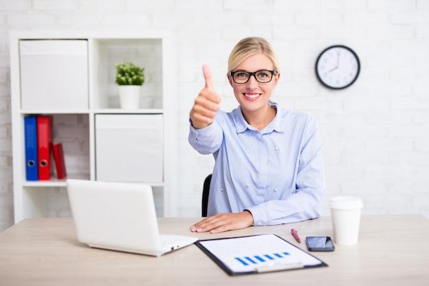 Vrolijke zakenvrouw zittend in een modern kantoor en duimen omhoog