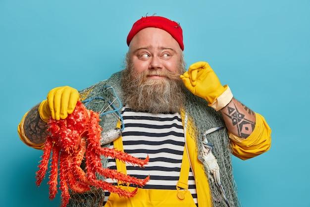 Vrolijke zeeman krult snor, houdt groot zeedier vast, gekleed in gestreepte trui en gele overall