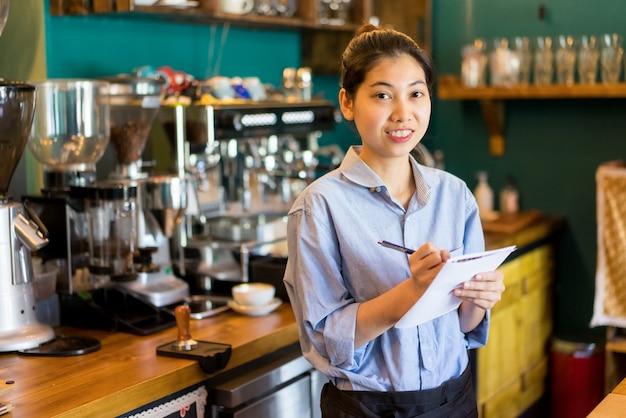 Vrolijke zekere aziatische serveerster die nota's in document maakt.